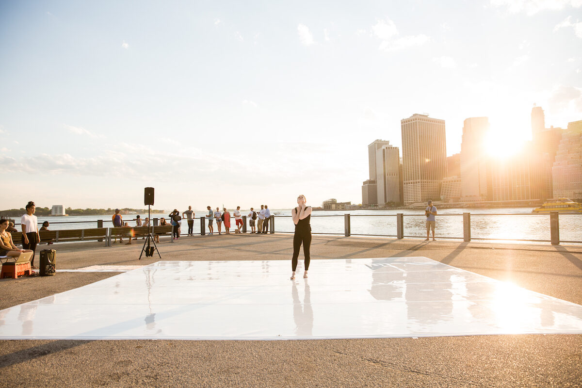 A white dancer standing on a marley floor in front of a New York City skyscape and river with the sun beaming behind them.