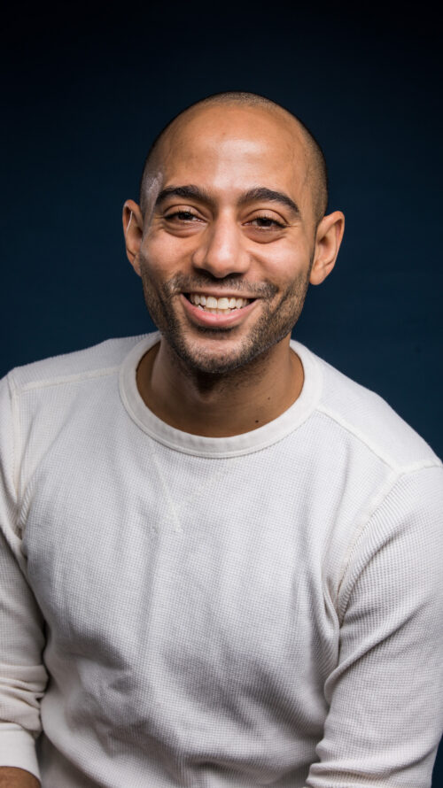Photo of a Black man smiling at the camera in a white shirt.