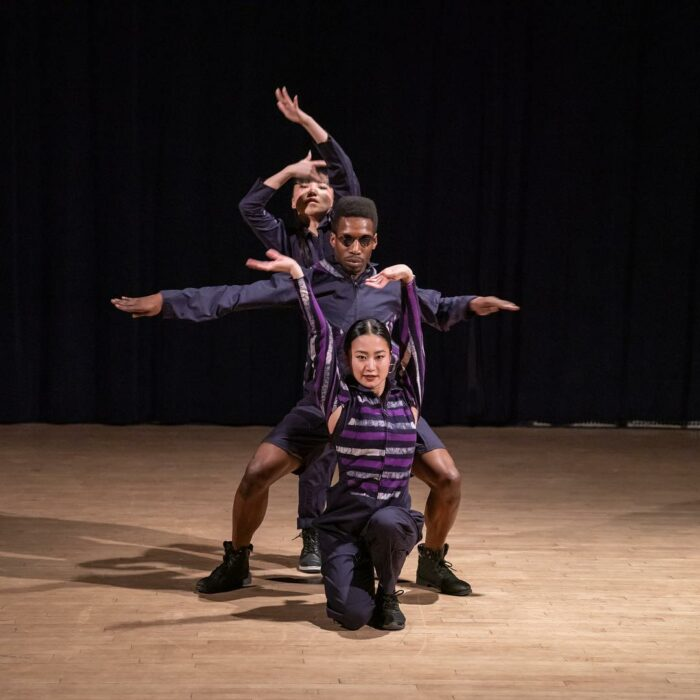 Omari Mizrahi and two dancers in a line formation.