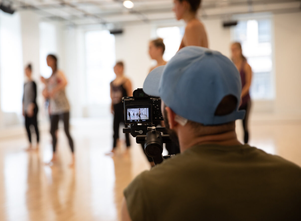 Person filming a group of dancers. The dancers are blurry and the camera is in focus.