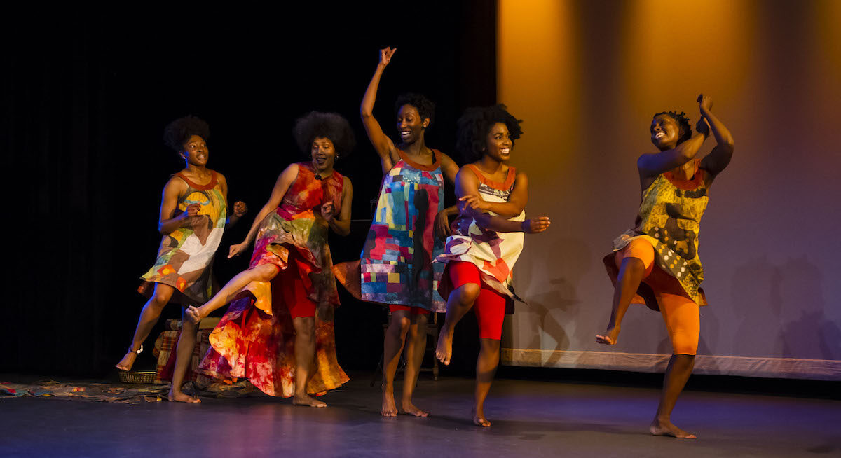 Group of black women smiling and dancing together on stage.