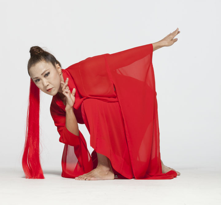 Asian woman in red dress looking into the camera.