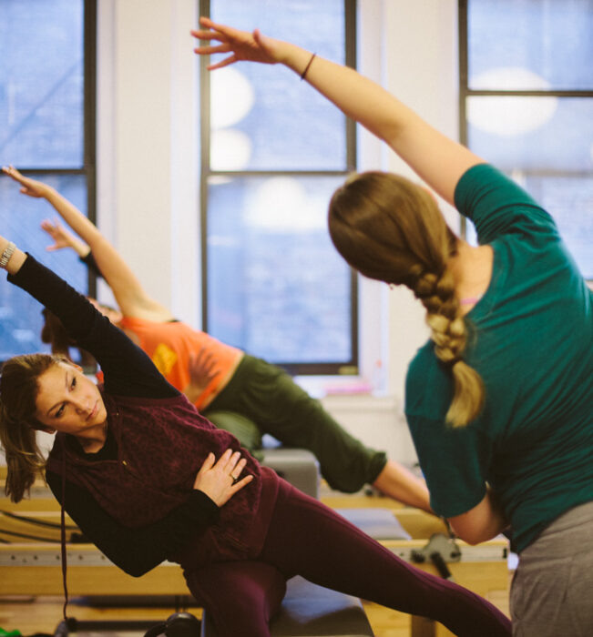 Two students following movement led by the standing Pilates instructor.
