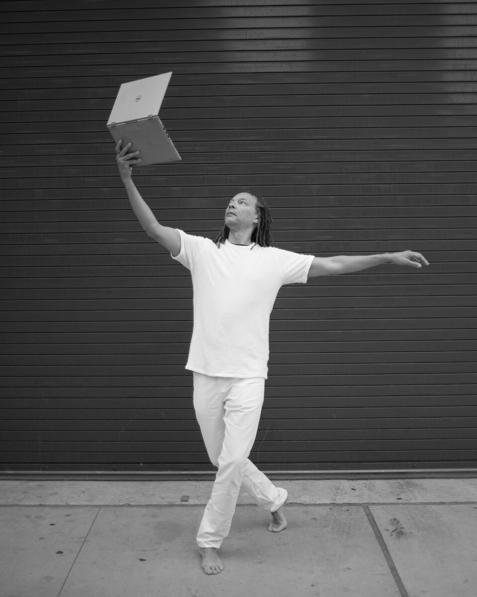 Man in a dance position holding a laptop in the air.