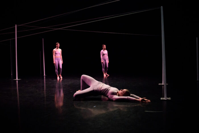 Three people on stage surrounded by a thread.