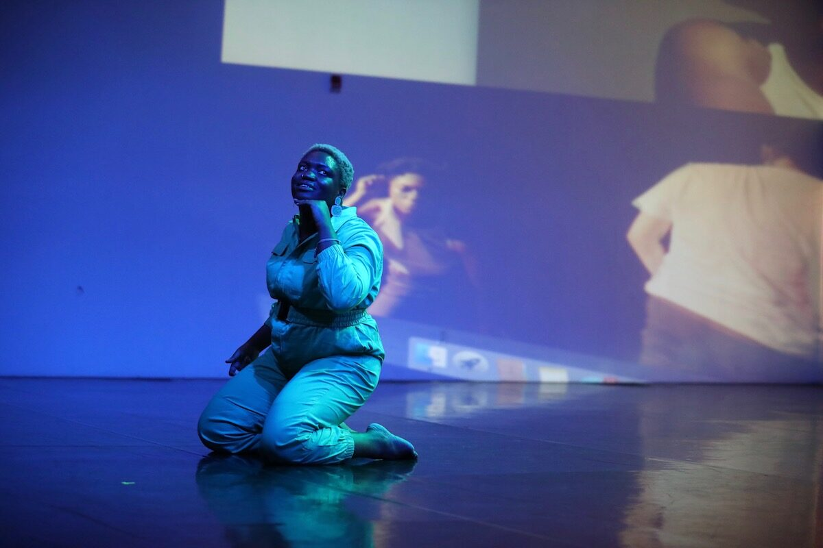 Ogemdi Ude kneeling on a saturated blue lit stage.