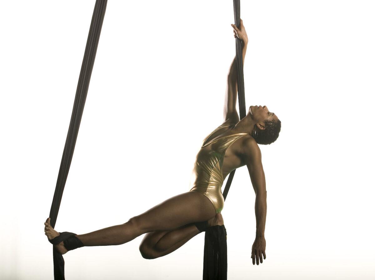 Black woman intertwined in aerial silks