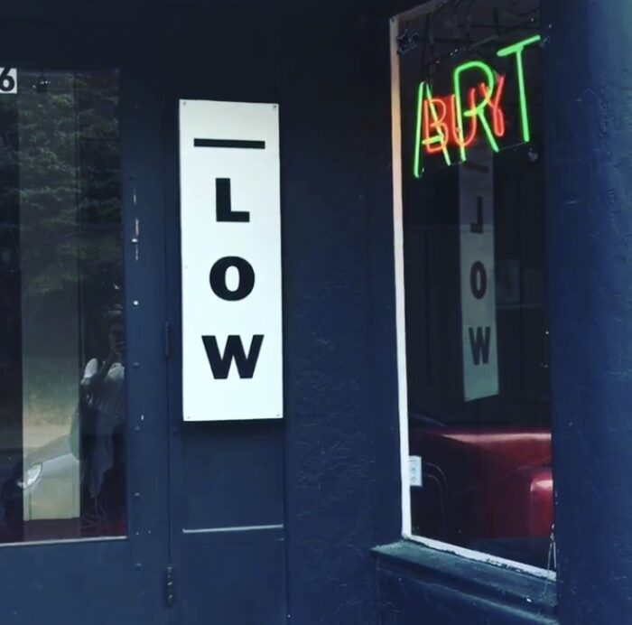 "A door with two signs that reads ""Low Art"""