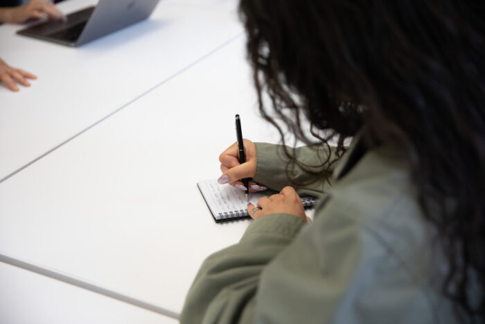 Woman writing in a notebook on a desk.