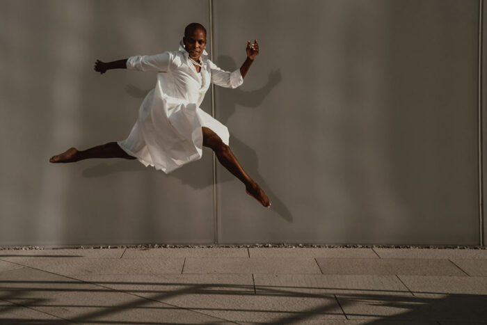 Hope Boykin leaps across the frame in profile, in a billowing white skirt.