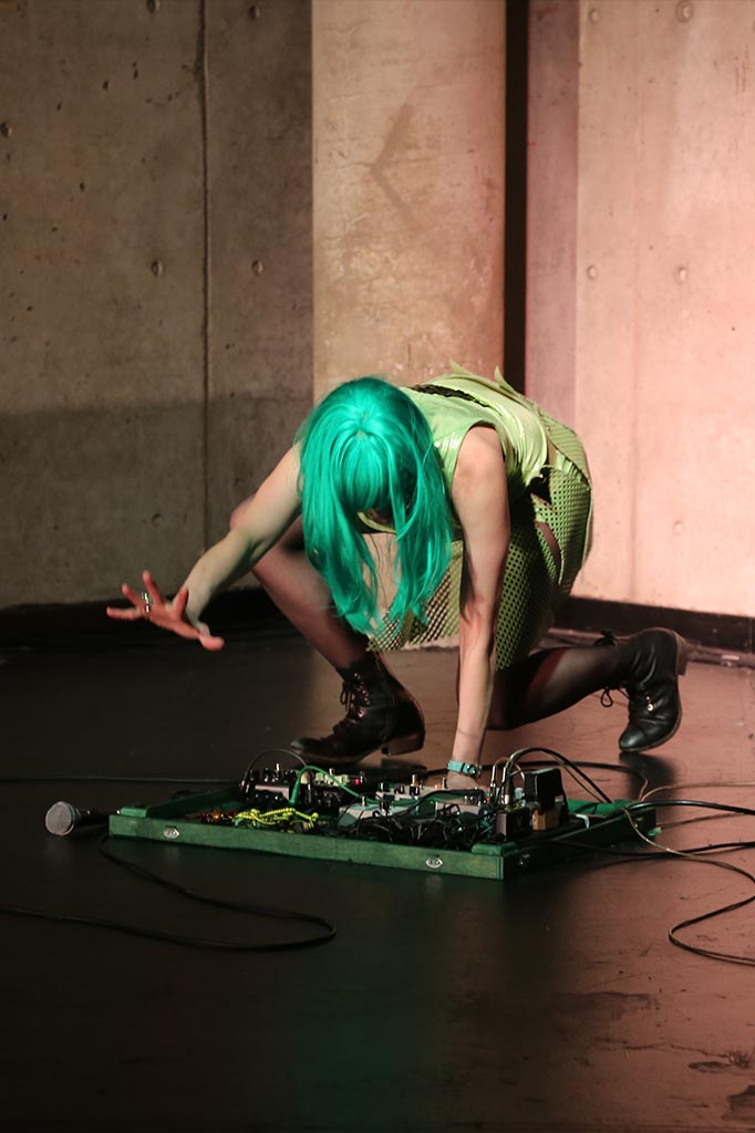 Leyya Mona Tawil as Lime Rickey International, crouching onstage with the right hand outstretched.