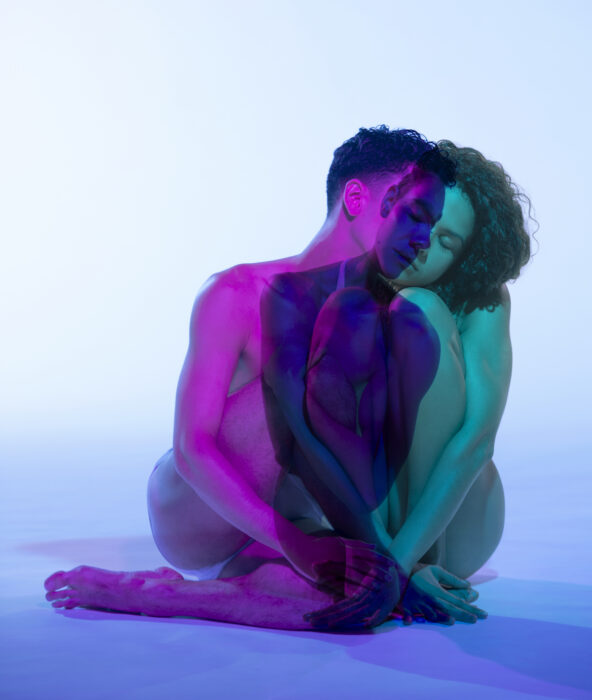 Two people's bodies saturated in purple and green. Their bodies overlap.