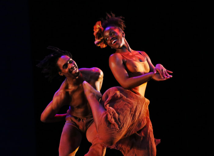 Two black dancers smiling and looking at each other on stage.