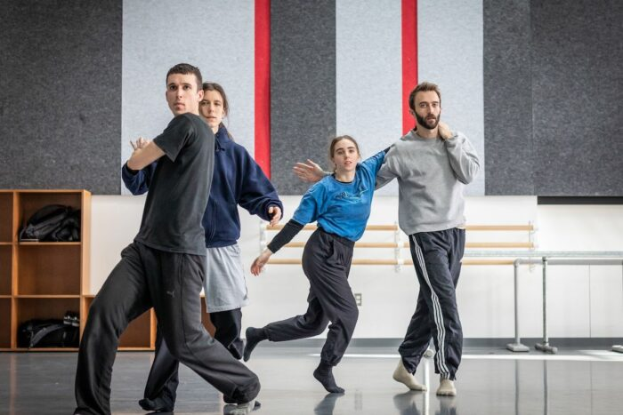 Group of white dancers moving in a dance studio.