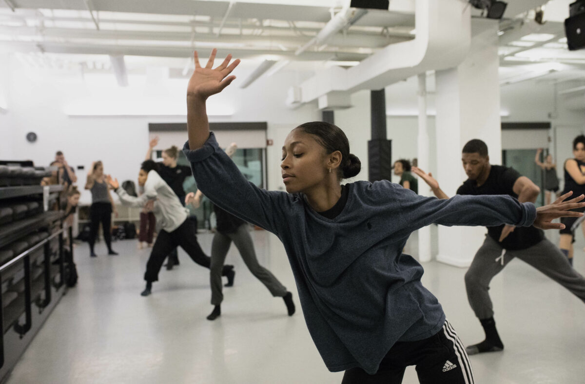Black woman dancing behind a group of students in dance class at Gibney 280.