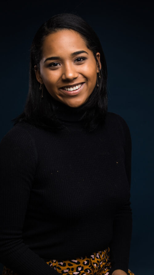 Woman of color smiling at the camera in a black turtle neck.