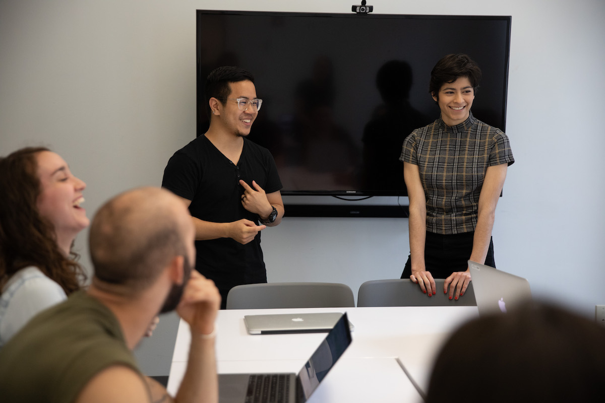 Four people talking and smiling in an office together.