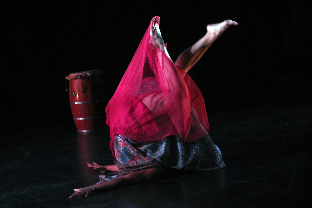 Woman in a red skirt, upside down on the floor.