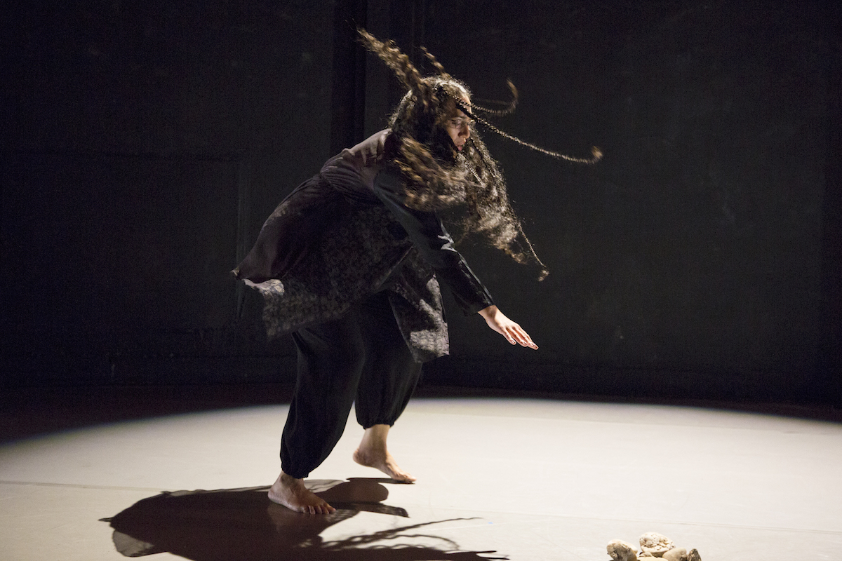 Woman dancing underneath a spotlight. Her hair flies in the air.