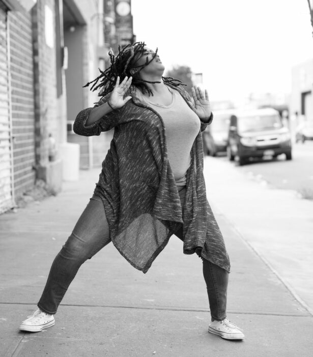 Black and white photo of a black woman dancing on the street.