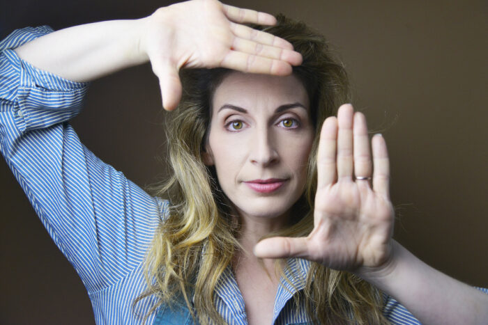 White woman with her hands framing her face as she looks into the camera.