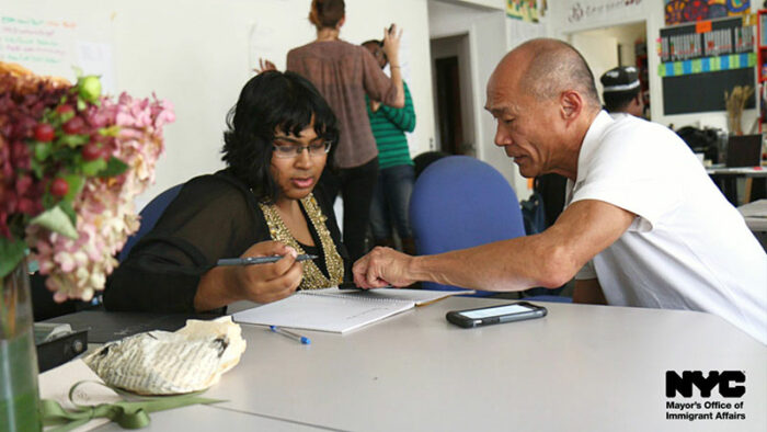 Asian man working with a woman of color with a pen and paper.