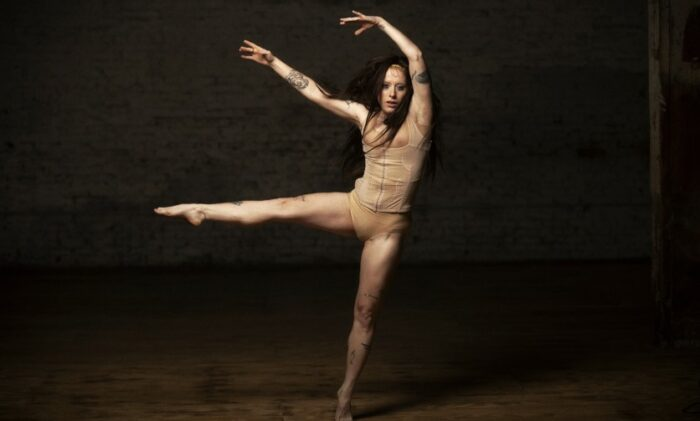 White woman in a ballet position, mid-motion in a nude suit.