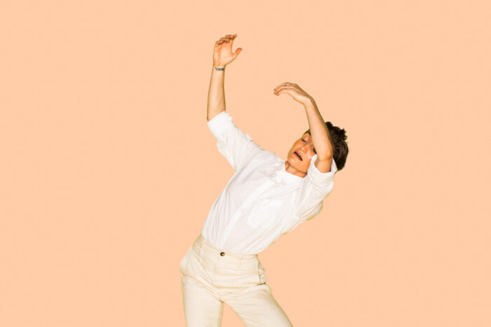 Woman in front of a peach background dancing.