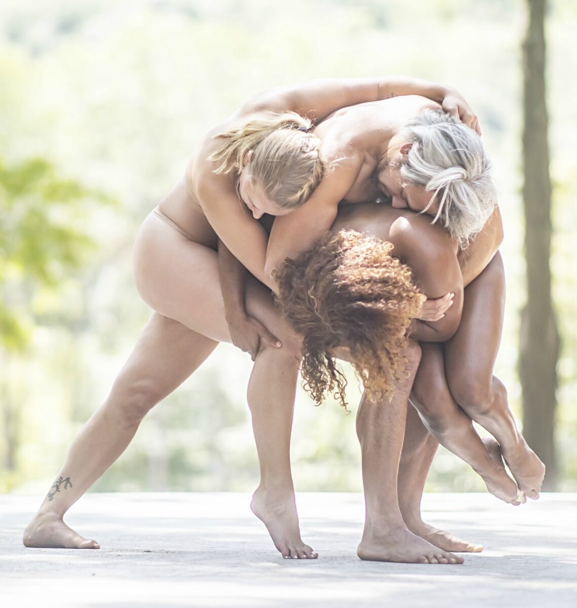 Three people nude a curled in a ball together on stage, in nature.