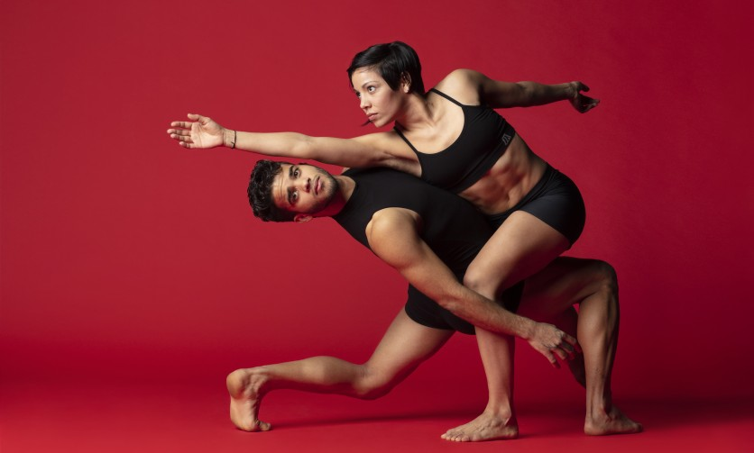 Two people of color dancing in front of a red background.