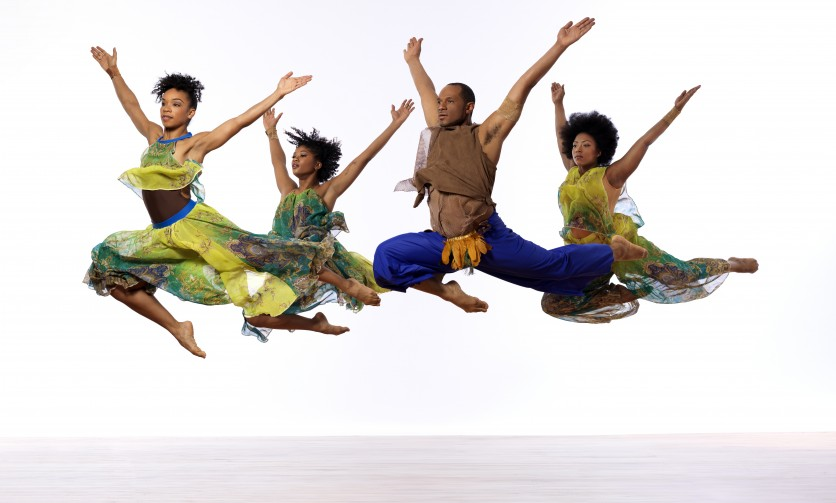 Four people jumping high in the air with their hands up.