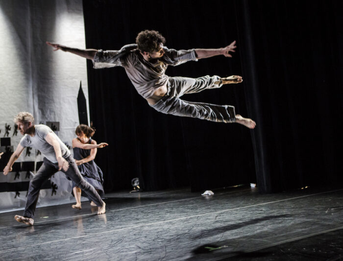 White male dancer high in the air with his legs sideways. Two people running behind him.