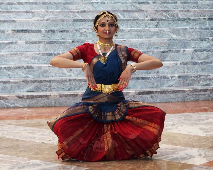Indian woman dressed in tradition garments as she performs a dance work.