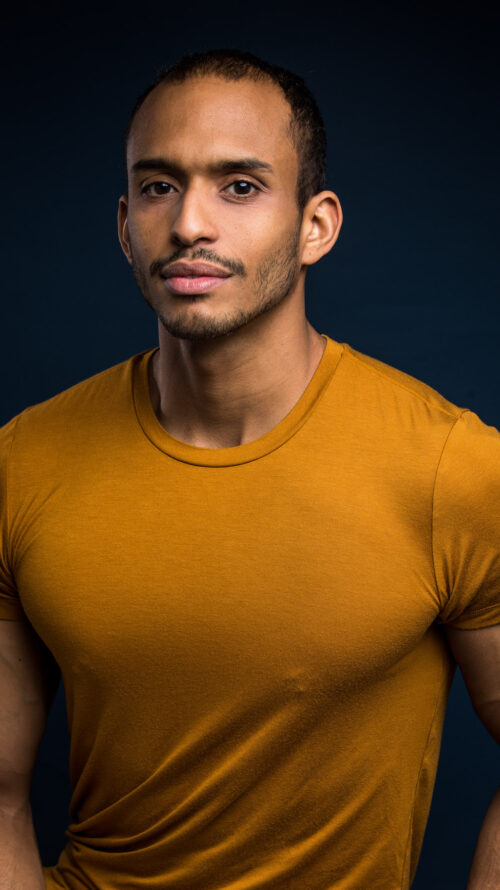 Man of color looking at the camera in a mustard colored tshirt.