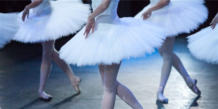 Cropped photo of ballerinas on stage in tutus.